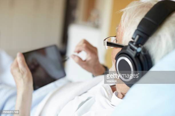 Over the shoulder view of senior man wearing headphones while using digital tablet in hospital