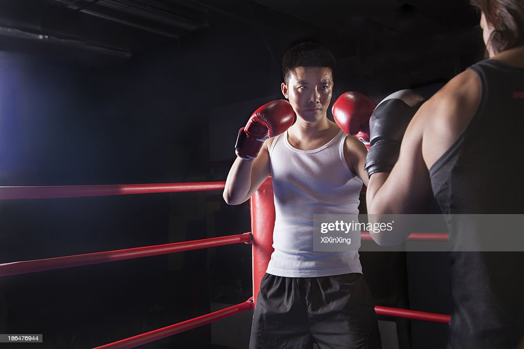 Over the shoulder view of two male boxers getting ready to box in the boxing ring in Beijing, China : Stock Photo