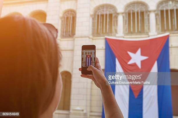 Over the shoulder view of young woman photographing Cuban flag on smartphone, Havana, Cuba