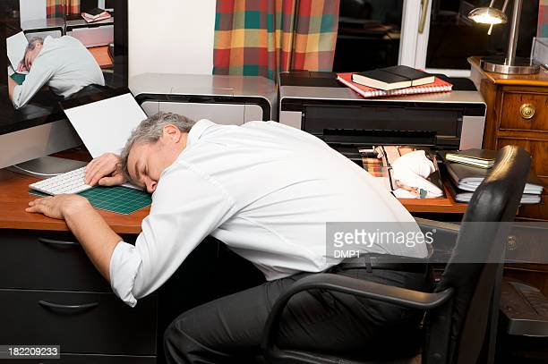 Over worked businessman asleep at home office desk at night.