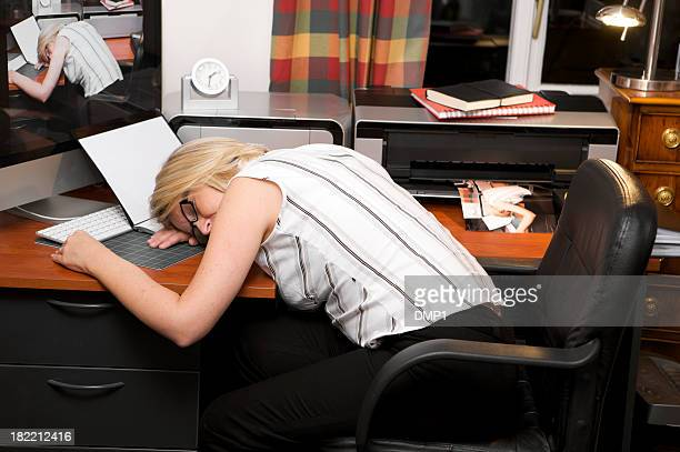 Over worked businesswoman asleep at home office desk at night.