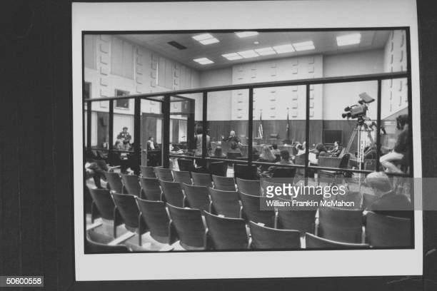 Overall interior view of courtroom w glass partition separating empty spectators seats fr trial area in front of the bench where reporters cameramen...