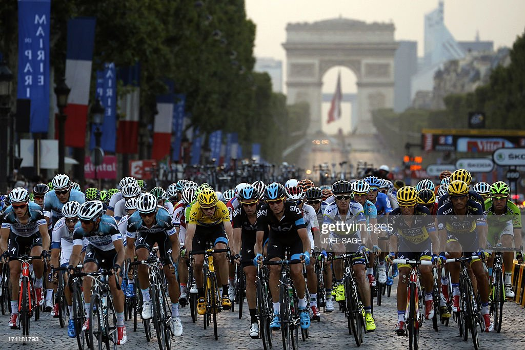 Overall leader's yellow jersey Britain's Christopher Froome and Spain's Alberto Contador (4th R) ride in the pack on the Champs Elysees avenue during the 133.5 km twenty-first and last stage of the 100th edition of the Tour de France cycling race on July 21, 2013 between Versailles and Paris.