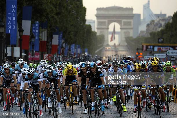 Overall leader's yellow jersey Britain's Christopher Froome and Spain's Alberto Contador ride in the pack on the Champs Elysees avenue during the...