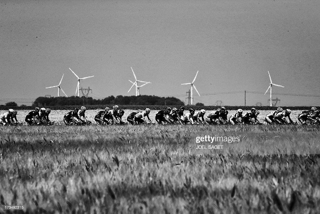 Overall leader's yellow jersey Britain's Christopher Froome (C) rides in the pack along wind turbines during the 173 km thirteenth stage of the 100th edition of the Tour de France cycling race on July 12, 2013 between Tours and Saint-Amand-Montrond, central France.