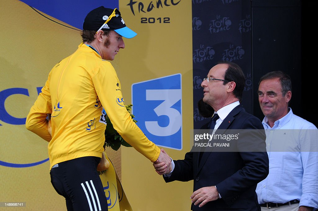 Overall leader's yellow jersey, British Bradley Wiggins (C), shakes hands with France's President Francois Hollande, next to Tour de France five-time winner, France's Bernard Hinault (R) as he leaves the podium at the end of the 222,5 km and eighteenth stage of the 2012 Tour de France cycling race starting in Blagnac and finishing in Brive-la-Gaillarde, southwestern France, on July 20, 2012.