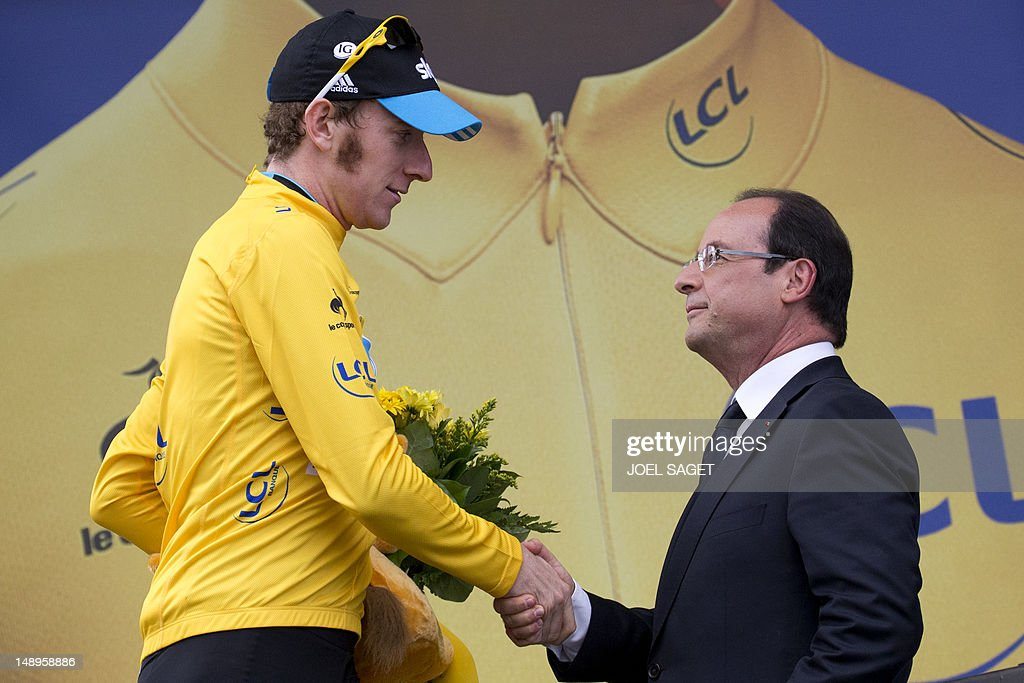 Overall leader's yellow jersey, British Bradley Wiggins (L), shakes hands with France's President Francois Hollande as he leaves the podium at the end of the 222,5 km and eighteenth stage of the 2012 Tour de France cycling race starting in Blagnac and finishing in Brive-la-Gaillarde, southwestern France, on July 20, 2012.