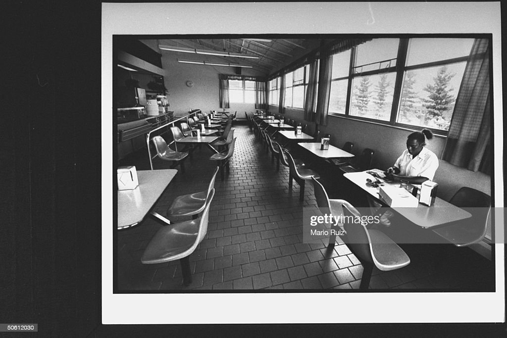 Overall view of large cafeteria with rows of booths and one black woman reading magazine at the Federal Correctional Institution where Leona Helmsley...