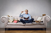 Young man is sitting on his couch surrounded by books