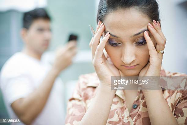 Overburdened young woman holding head in hand out of headache.