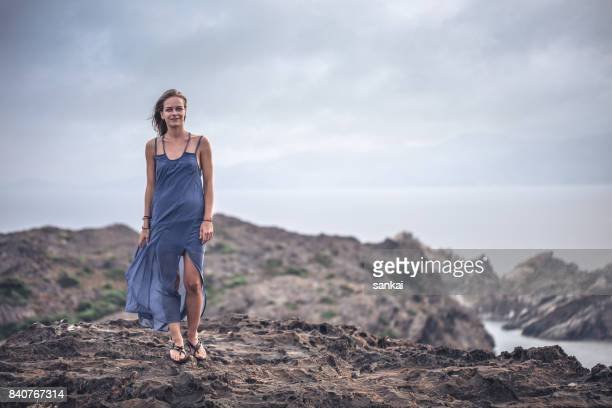 Overcast sky over lonely woman standing alone at the rocky coast