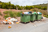 Overflowing bins next to Orange Orchard, Valencia region, Spain