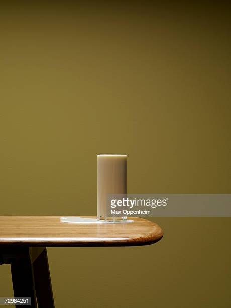 Overflowing glass of milk on table