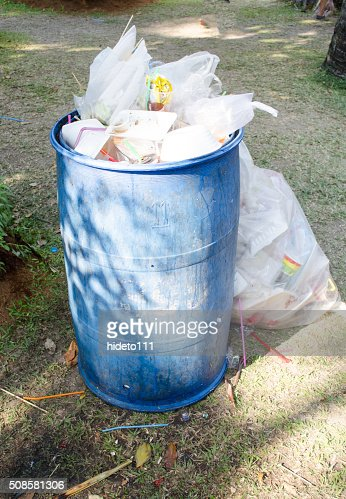 overflowing green garbage bin : Stock Photo