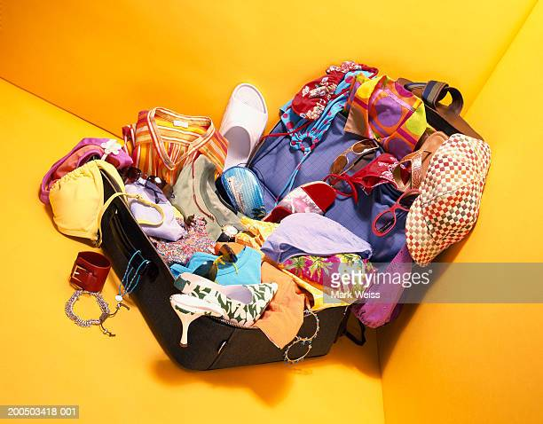 Overflowing suitcase on yellow background