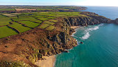 Drone pictures of the picturesque sandy beach of Porthcurno on a sunny afternoon, featuring the coastline and aquamarine Atlantic ocean