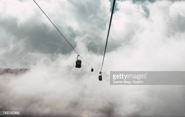 Overhead Cable Car Against Cloudy Sky In Foggy Weather