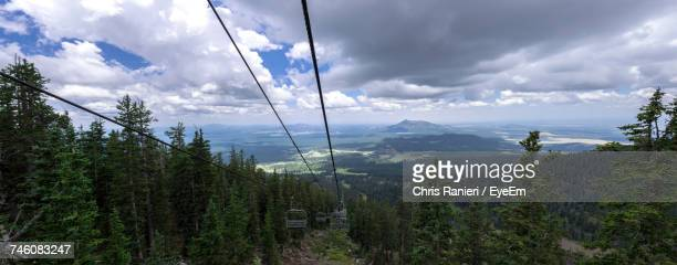 Overhead Cable Cars On Mountains Against Cloudy Sky
