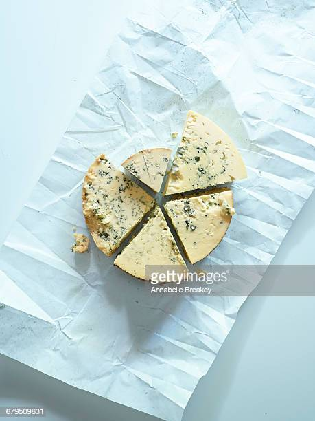 Overhead cut blue cheese wheel on parchment pap
