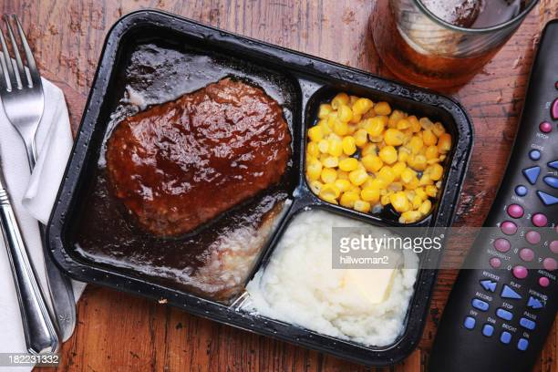 Overhead image of a TV dinner on a wood table