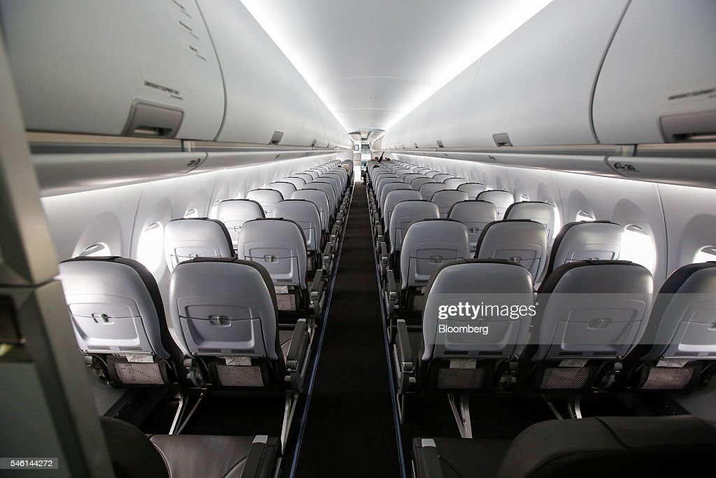 Overhead lockers hang above seats in the Sukhoi Superjet 100 aircraft manufactured by Sukhoi Civil Aircraft Co on the opening day of the Farnborough...