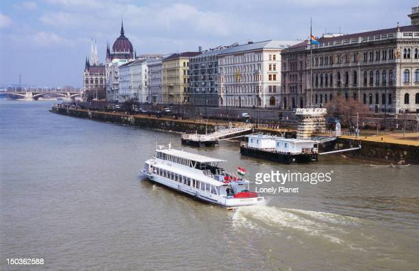 Overhead of cruise boat on Danube River and Buda riverbank.