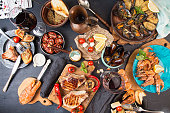 Overhead of dinner table. Assorted delicious grilled barbecue meat and seafood with vegetable. Pork grilled steaks, grilled salmon trout, mussels, shrimps, dried tomato, cherry tomato, chilii pepper,