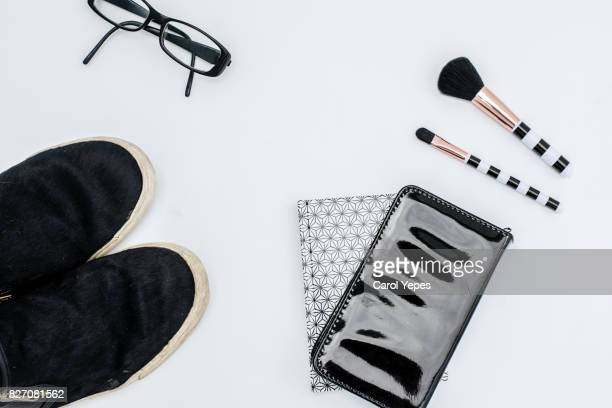 Overhead of essentials of a modern woman. Cosmetic objects and note books on white background