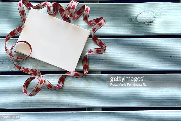 Overhead of Festive greeting card surrounded by ribbon. Add your own text. Subjects captured against soft window lighting. Copy space.