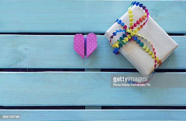 Overhead of handmade gift with vibrant bow tie and origami heart shape on blue wooden background and copy space. Subjects captured against soft window lighting