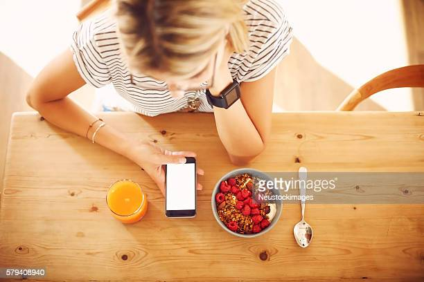 Overhead of hipster with smart phone and breakfast at table