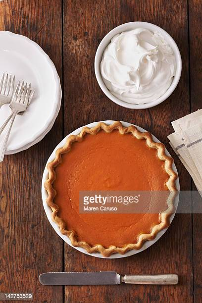 Overhead of pumpkin pie and bowl of whipped cream