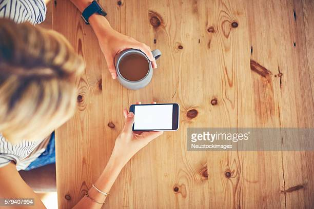 Overhead of young woman using smart phone at wooden table