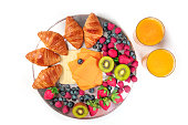Overhead photo of hotel breakfast ingredients on white background. Croissants, cheese, fresh fruit including strawberries, raspberries, blueberries, and kiwis, with orange juice and copy space