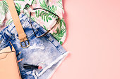 Overhead shot of female casual clothes on pink background