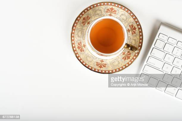 Overhead Shot of Tea Cup Plate and Computer Keyboard on White Table with Blank Space