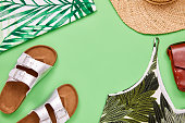 Flat lay shot of summer vacation accessories. Overhead shot of top sandal sun hat and leather purse. They are arranged on green background.