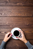 Overhead shot of woman's hands holding cup of coffee. Close up