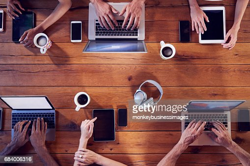 Overhead shot of young adults using technology at a table : Stock Photo