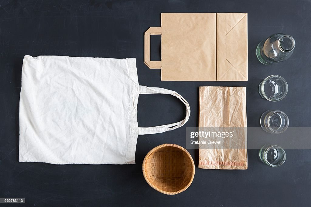 Overhead still life of reusable and paper bags and glasses