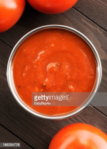 Overhead view of a bowl of tomato sauce next to tomatoes