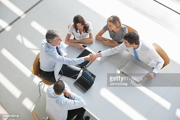 overhead view of a business group in a meeting shaking hands