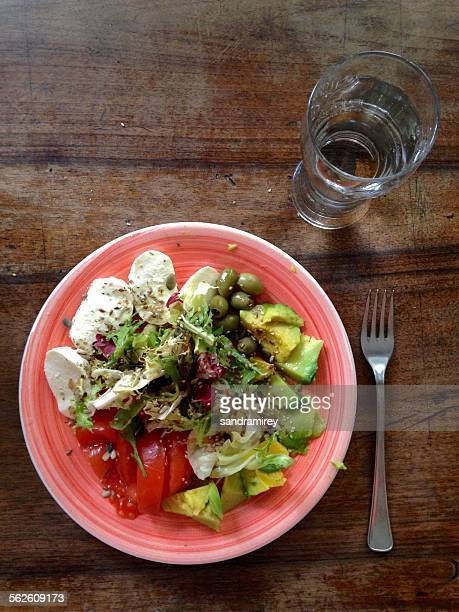 Overhead view of a plate of salad with a  glass of water