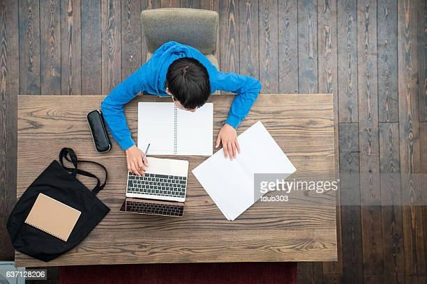 Overhead view of a teenage boy doing homework