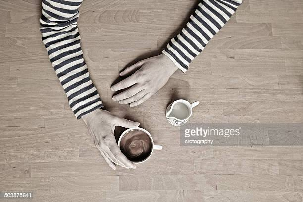 Overhead view of a woman sitting at a table with a cup of coffee