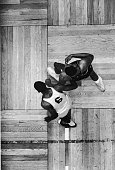 Overhead view of American professional basketball player Wilt Chamberlain of the Philadelphia 76ers as he battles for position with Bill Russell of...