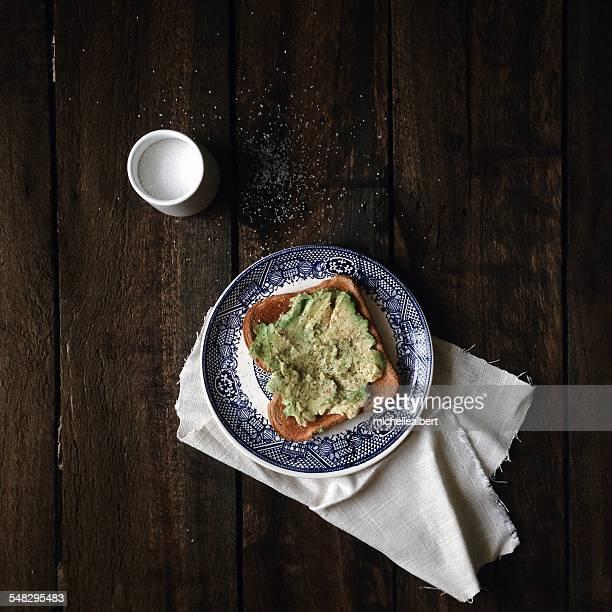 Overhead view of avocado toast breakfast with salt pot