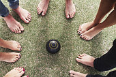 Overhead view of bare feet friends on grass around lawn bowls