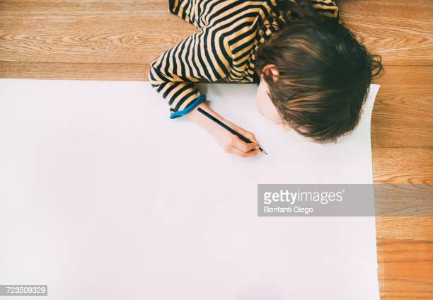 Overhead view of boy drawing on large paper on floor
