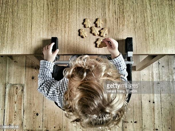 Overhead view of boy with gingerbread cookies at table